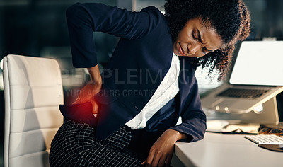 Buy stock photo Shot of a young businesswoman suffering with back pain while working in an office at night