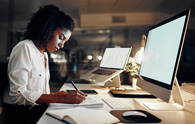 Buy stock photo Shot of a young businesswoman going through paperwork while working in an office at night