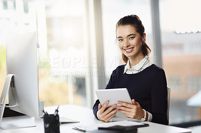 Buy stock photo Portrait of an attractive young businesswoman sitting at her desk and using a tablet in a modern office