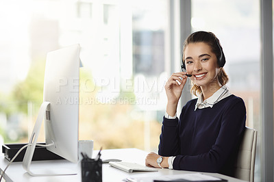 Buy stock photo Portrait of a smiling attractive young businesswoman wearing a headset and sitting at her desk in a modern office