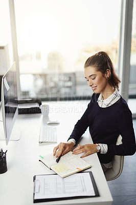 Buy stock photo Shot of an attractive young businesswoman sitting at her desk and reading notes in a modern office