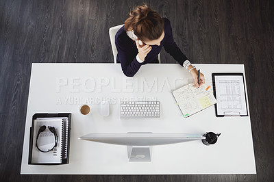 Buy stock photo Aerial shot of an unrecognizable young businesswoman sitting at her desk and talking using her tablet in a modern office
