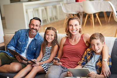 Buy stock photo Shot of a happy young family using wireless devices on the sofa at home