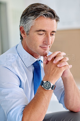 Buy stock photo Shot of a confident mature businessman wearing a suit and sitting on a sofa indoors with his hands clasped