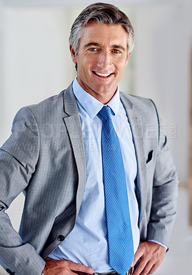 Buy stock photo Portrait of a confident mature businessman wearing a suit and standing indoors with his hands on his hips
