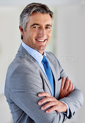 Buy stock photo Portrait of a confident mature businessman wearing a suit and standing indoors with his arms crossed