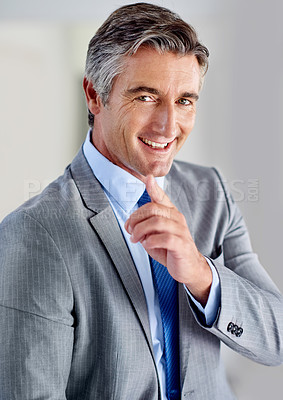 Buy stock photo Portrait of a confident mature businessman wearing a suit and standing indoors while pointing at the camera