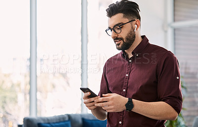 Buy stock photo Shot of a handsome young businessman using a cellphone in his office at work