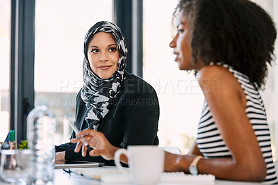 Buy stock photo Shot of two young businesswomen having a meeting together at work