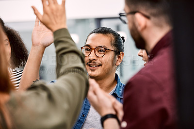 Buy stock photo Shot of a group of young businesspeople celebrating and giving each a high five in their office at work