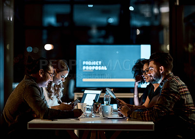 Buy stock photo Shot of a group of young businesspeople using smart devices during a late night meeting at work