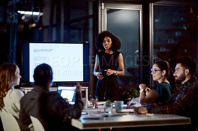 Buy stock photo Shot of a young businesswoman delivering a presentation during a late night meeting at work