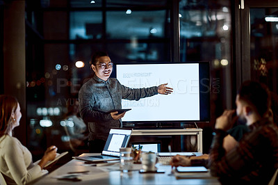 Buy stock photo Shot of a young businessman delivering a presentation during a late night meeting at work