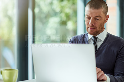 Buy stock photo Cropped shot of a handsome middle aged  businessman working on a laptop in his office