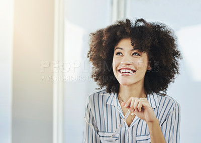 Buy stock photo Shot of a cheerful young businesswoman looking thoughtful in her office at work