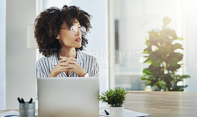 Buy stock photo Shot of an attractive young businesswoman looking thoughtful while working in her office at work