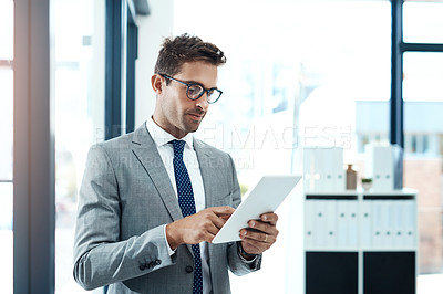 Buy stock photo Shot of a professional businessman using a digital tablet in his office
