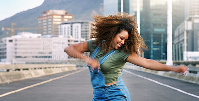 Buy stock photo Shot of an attractive young woman performing a street dance routine during the day while outdoors