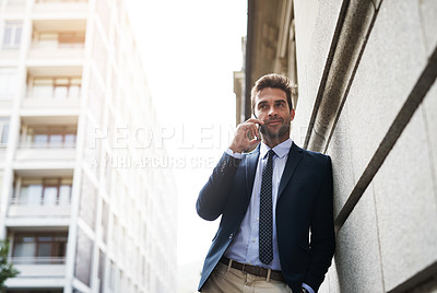 Buy stock photo Portrait of a handsome young businessman talking on his cellphone while heading to work in the morning