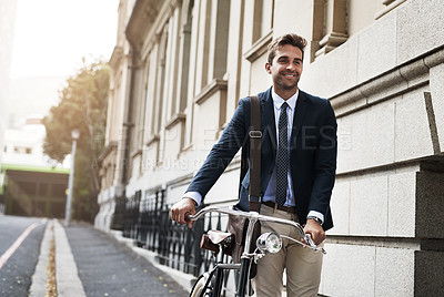 Buy stock photo Shot of a handsome young businessman pushing his bicycle while making his way to work in the morning