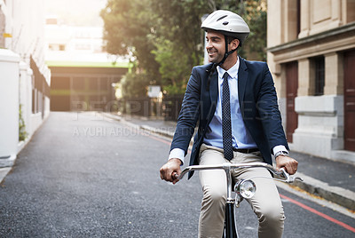 Buy stock photo Shot of a handsome young businessman riding his bicycle to work in the morning