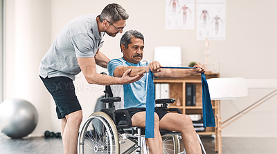 Buy stock photo Shot of a senior man in a wheelchair exercising with a resistance band along side his physiotherapist