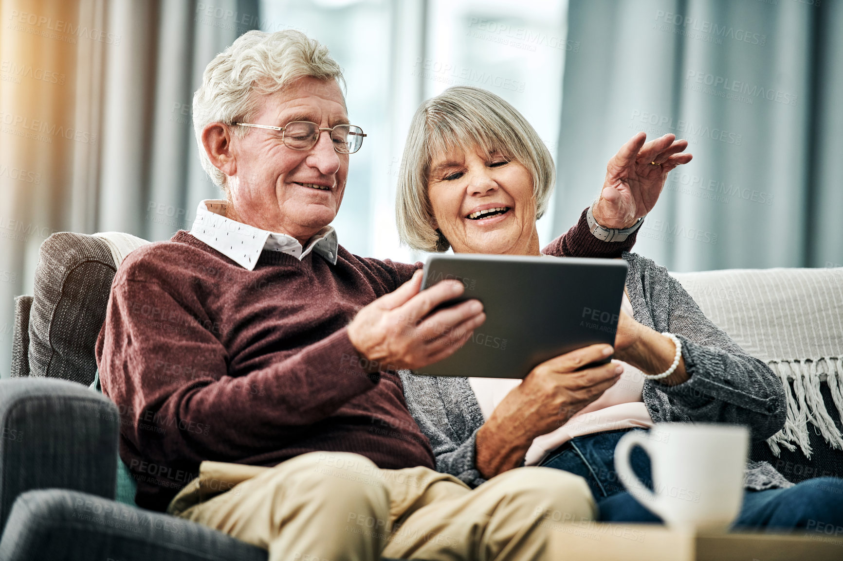 Buy stock photo Shot of a happy elderly couple using a digital tablet while relaxing on the sofa together at home