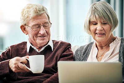 Buy stock photo shot of an affectionate senior couple using a laptop while sitting on their living room sofa at home