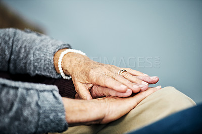 Buy stock photo Shot of an unrecognizable senior couple's holding hands while relaxing at home