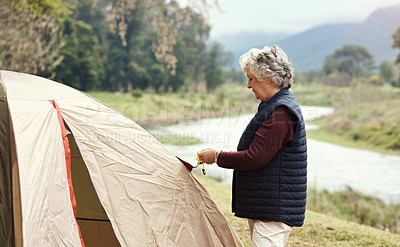 Buy stock photo Cropped shot of a senior woman setting up a tent at her chosen camping spot