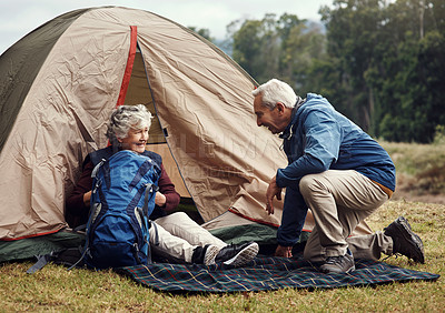 Buy stock photo Full length shot of an affectionate senior couple relaxing at their chosen camping spot