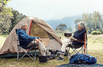 Buy stock photo Full length shot of an affectionate senior couple relaxing on their chosen camping spot