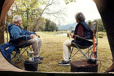 Buy stock photo Full length shot of an affectionate senior couple enjoying coffee while relaxing at their chosen camping spot