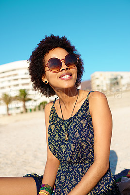 Buy stock photo Cropped shot of an attractive young woman wearing casual clothes while sitting on the beach alone and enjoying the sunshine
