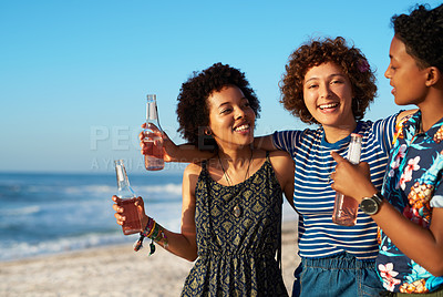 Buy stock photo Shot of an attractive young trio of women enjoying a day out together on the beach during the day