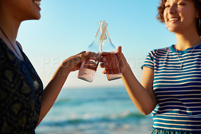 Buy stock photo Shot of two attractive young women celebrating and having a drink together on the beach during the day