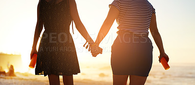 Buy stock photo Rearview shot of two unrecognizable young women holding hands on the beach at sunset