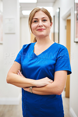 Buy stock photo Portrait of an attractive young nurse posing with her arms folded at a clinic