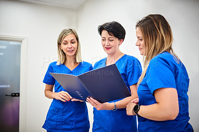 Buy stock photo Shot of three young female nurses discussing some paperwork at a clinic