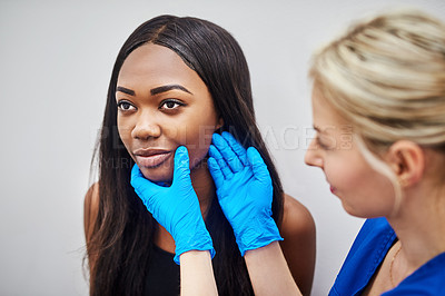 Buy stock photo Shot of a beautiful young woman getting her face analyzed by a nurse against a grey background