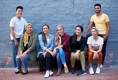 Buy stock photo Portrait of an young group of muslim friends posing together against a grey brick outside wall