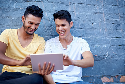Buy stock photo Cropped shot of two handsome young men sitting against a gray brick wall while using their tablet during the day