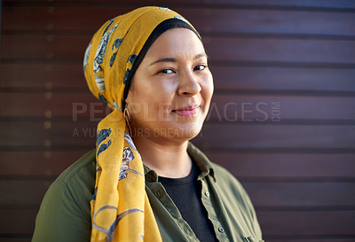 Buy stock photo Headshot of an attractive young woman wearing a headscarf and smiling alone against a wooden background outside