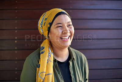 Buy stock photo Headshot of a single attractive young woman wearing a headscarf and laughing against a wooden background outside