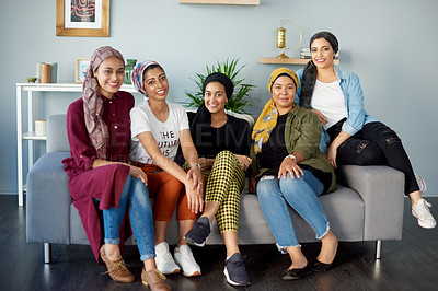 Buy stock photo Full length shot of an attractive young group of women wearing headscarves and sitting on a sofa indoors