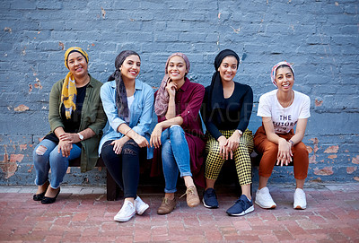 Buy stock photo Full length shot of an attractive young group of women wearing headscarves and sitting against a gray brick wall outside