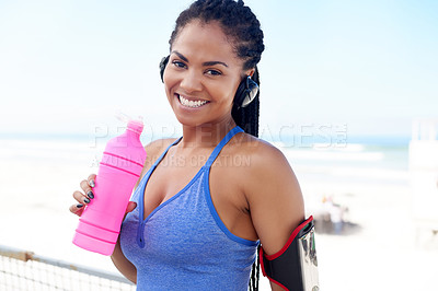 Buy stock photo Portrait of an attractive young woman holding a water a bottle while exercising outdoors