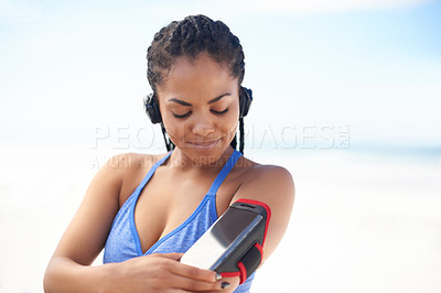 Buy stock photo Shot of an attractive young woman listening to music while exercising outdoors
