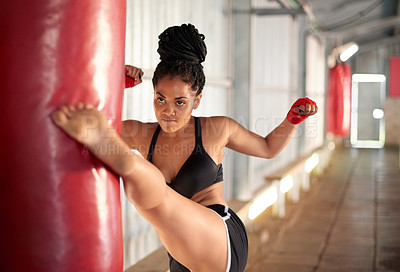 Buy stock photo Shot of a sporty young woman working out with a punching bag