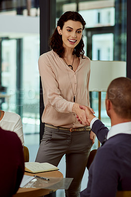 Buy stock photo Shot of two businesspeople shaking hands in agreement during a boardroom meeting at work